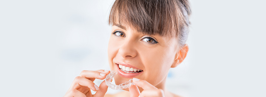 young woman inserting teeth aligners