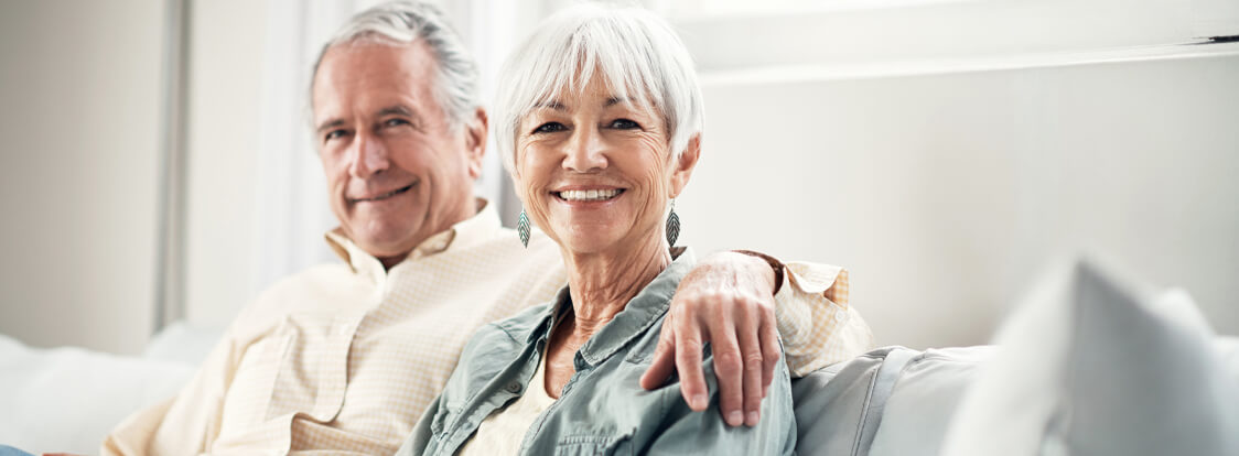 An older couple with dental veneers smiling on a couch