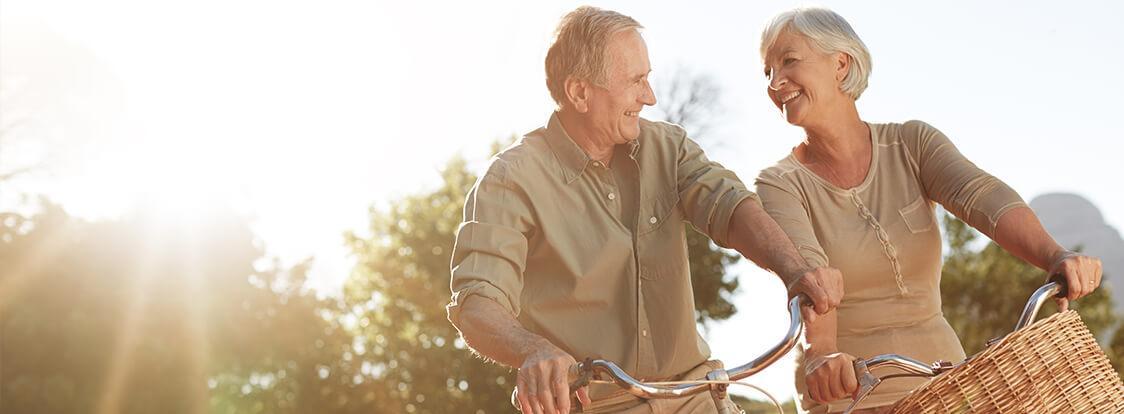 an elderly couple smiling as they ride bikes in the sunset