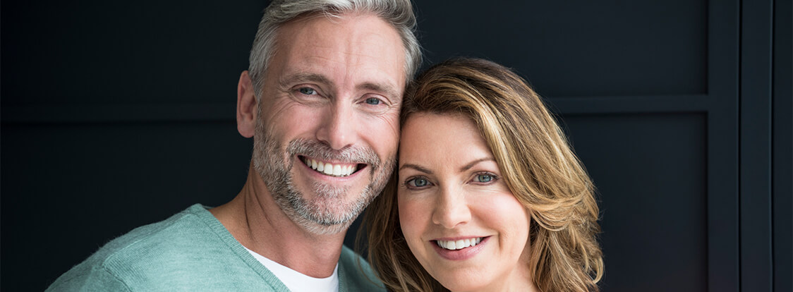 A couple smiling after dental crowns