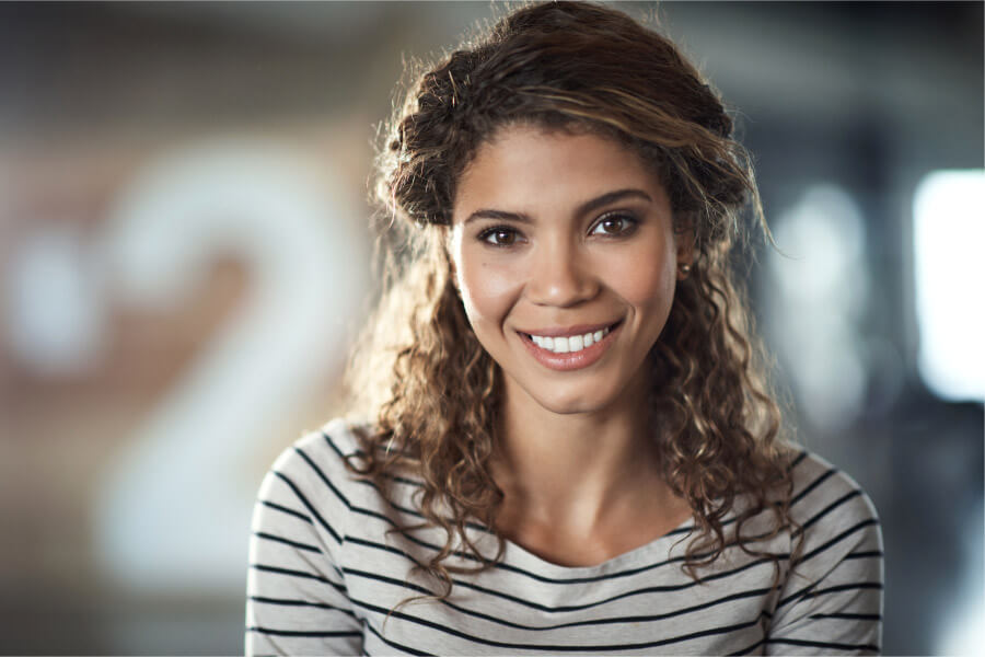 Curly brunette woman smiles after her smile makeover consultation in Tucson, AZ, at Artistic Dentistry