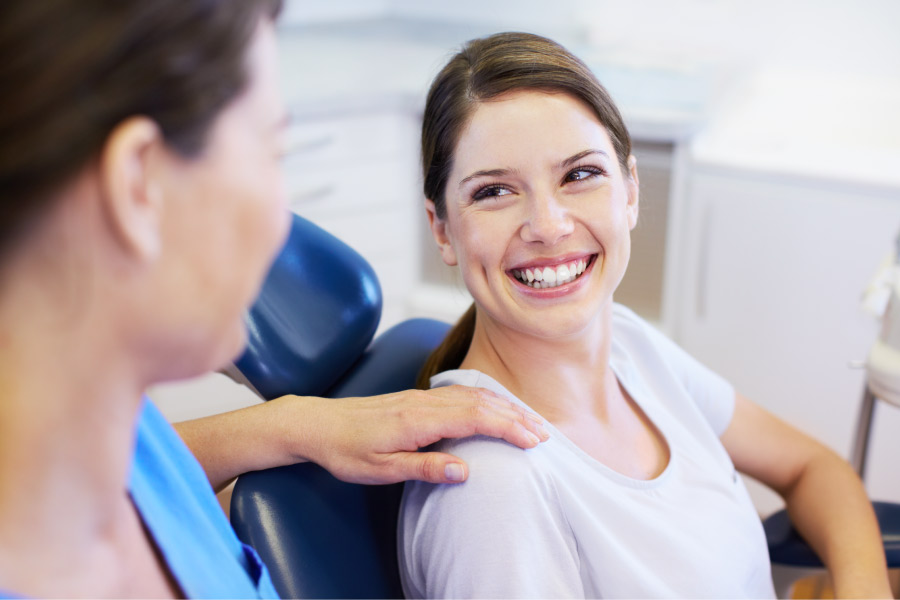 Brunette woman smiles at the dentist before receiving a routine cleaning and checkup in Tucson, AZ