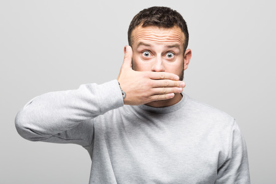 Brunette man covers his mouth in embarrassment due to bad breath